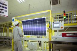 Trabajador con traje de protección ante un módulo solar
