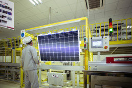 Worker in protective clothing in front of solar module