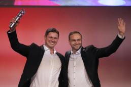 zwei Männer vor roter Wand halten Preis in die Luft