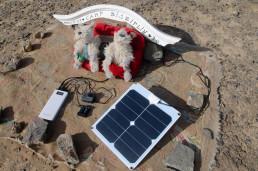 Kuscheltiere im Sand mit Solarmodul und Powerbank