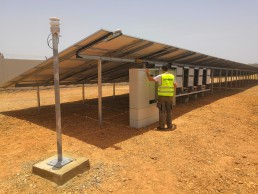 craftsman with yellow vest installs PV-diesel hybrid power plant in the desert