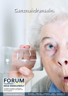old woman hocht with drinking glass at her ear on the wall