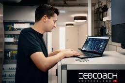 Mann steht und arbeitet am Laptop