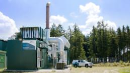 Blockheizkraftwerk vor Bäumen und blauem Himmel