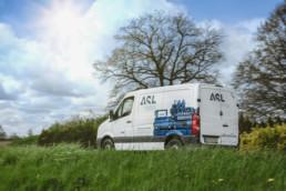 Einsatzfahrzeug von ASL fährt an Wiesen und Bäumen vorbei