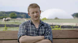 Junger Mann sitzt auf Bank, im Hintergrund Weide und Gasspeicher