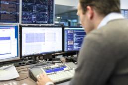 Mitarbeiter der Energiehändlerin Alpiq am Schreibtisch vor mehreren Bildschirmen