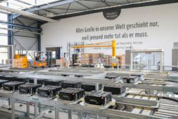 Blick auf eine Fabrik. Im Vordergrung sind Batterien zusehen. Im Hintergrund sind ein Gabelstapler und zwei Männer zu sehen. An der Wand steht der Spruch