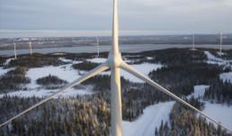 Blick auf eine winterliche skandinavische Waldlandschaft. Im Vordergrund befindet sich ein Windrad. Im Hintergrund sind weitere Windräder sowie ein Fluss zu erkennen.
