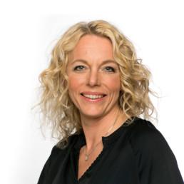 Porträtfoto einer Frau mittleren Alters in schwarzer Bluse vor einem weißen Hintergrund, die in die Kamera lächelt. Sie hat blonde wellige Haare.