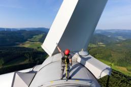 Mann steht auf der Gondel eines Windrads und berührt ein Rotorblatt. Hinter ihm ist der Schwarzwald und strahlend blauer Himmel zu sehen.