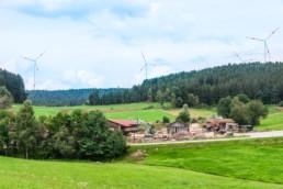 Vier Windräder im Hintergrund eines Sägewerks inmitten von Wiesen und Wald