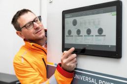 A man in work clothes touches a touchscreen with his hand, which he uses to control the entire microrid.