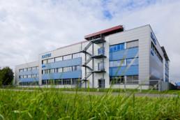 Auf dem Bild ist das Fertigungsgebäude in Memmingen zu sehen. Im Vordergrund ist eine grüne Wiese. Das Foto ist aus der Froschperspektive aufgenommen. Im Hintergrund sieht man das grau und blaue Firmengebäude.
