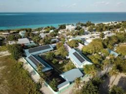 Photovoltaikanlage auf Dächern eines Gebäudes auf einer Insel der Malediven mit dem Meer im Hintergrund.