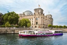 Ein Schiff fährt auf der Spree vor dem Deutschen Bundestag.