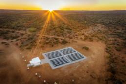 Solarmodule und weiße Container stehen in der Gibson-Wüste im Sonnenuntergang