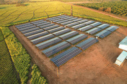 Solar modules stand outdoors, surrounded by fields. Next to the modules is a container